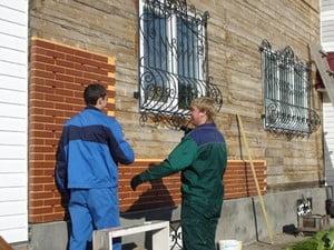 Процесс облицовки фасадной стены кирпичом