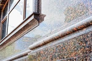 Стена дома, облицованная коричневым гранитом