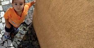 Ребенок возле оштукатеренной стены