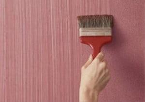 Широкой кистью красят стену