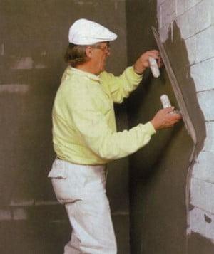 Мужчина шпаклюет фасад